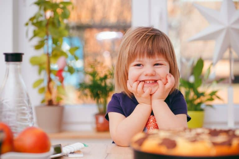 child with smile sitting at table